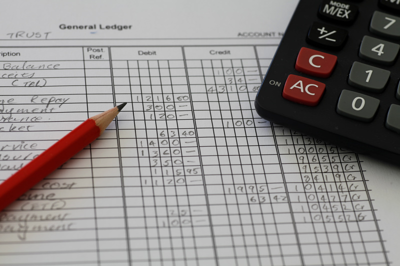 Bookkeeping paper with debit and credit numbers with pencil and calculator