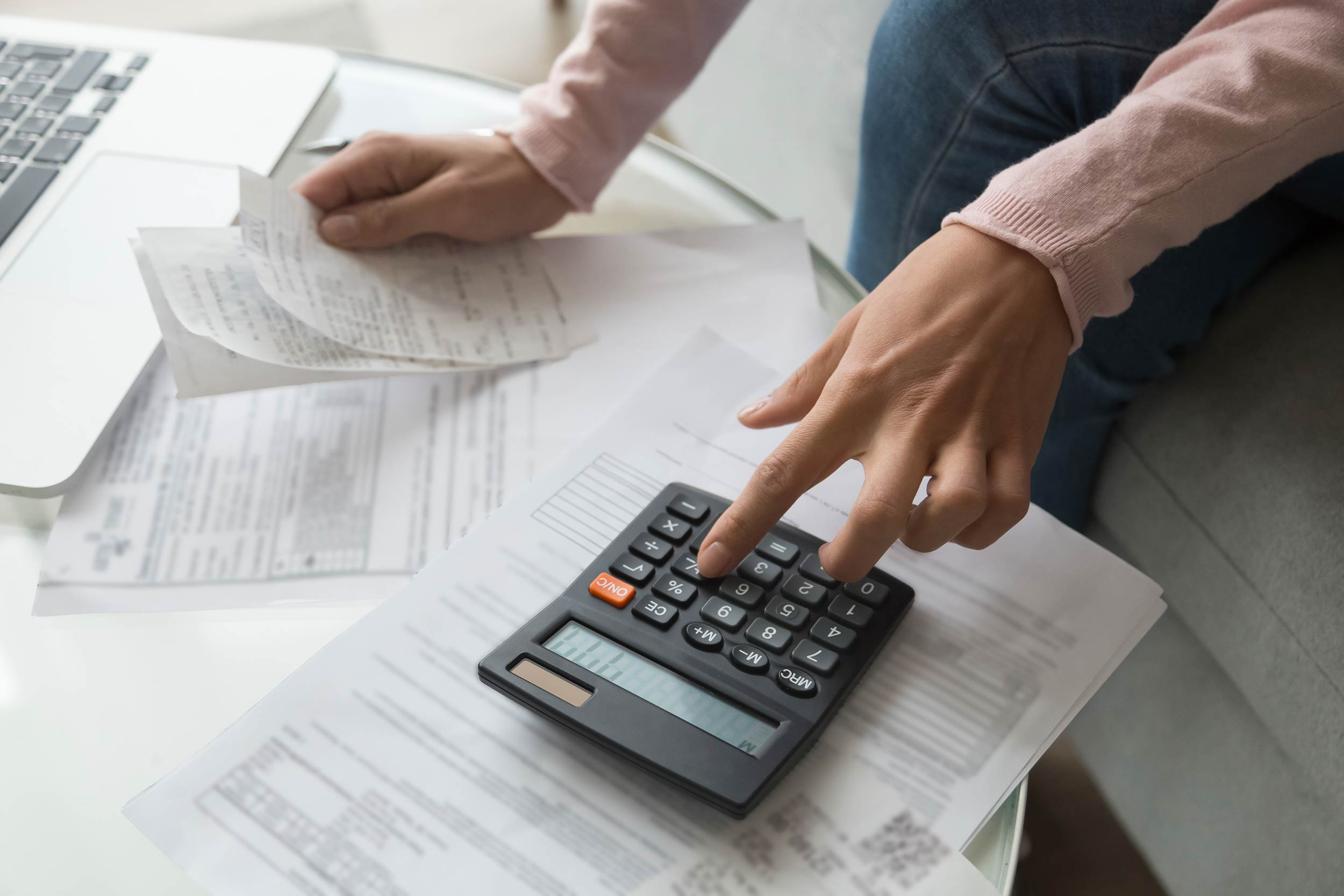 Bookkeeping at home with papers and calculator on table