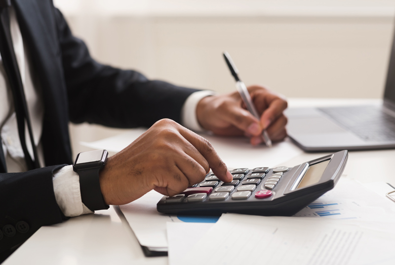 Businessman checking accounts and income with calculator