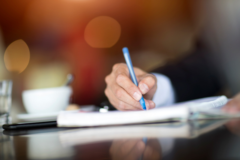 business person writing a letter on paper with a blue pen