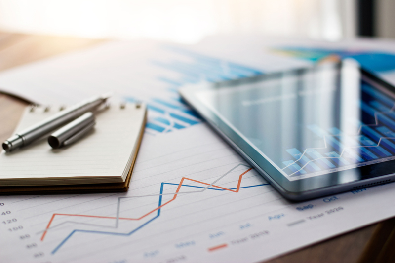 financial reports on table with pen, paper and tablet
